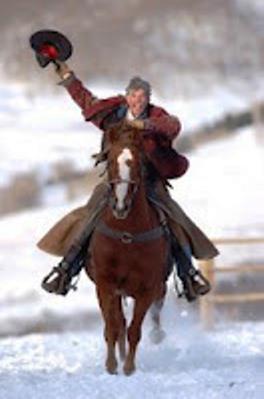 cowboy galloping on horse waving his hat