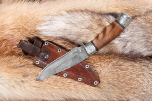 Hunting knife from braided hurlled on background of the fur