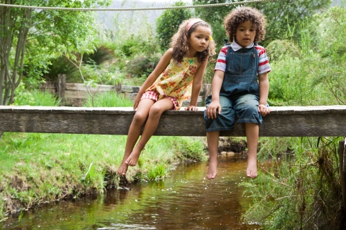Girl and boy on footbridge over stream