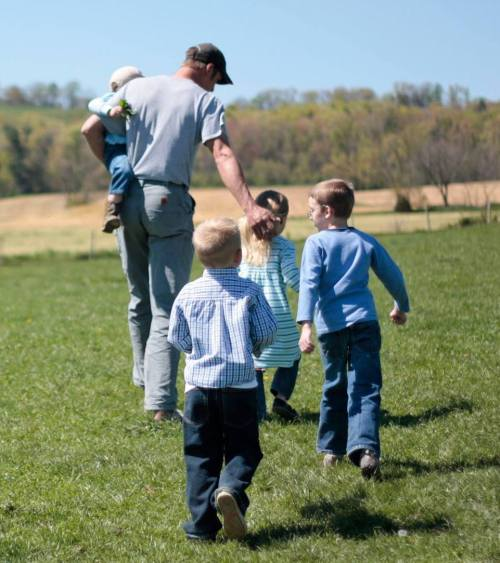 children with farmer in meadow