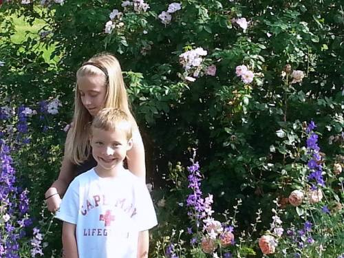 Emma and Owen beside the old pink rose with larkspur1