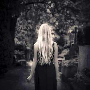 Blond girl walking alone at cemetery
